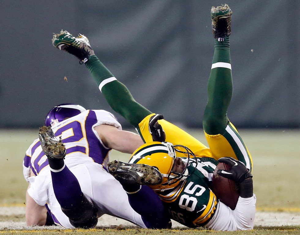 . Green Bay Packers wide receiver Greg Jennings (85) is hit by Minnesota Vikings free safety Harrison Smith (22) during their NFL NFC wildcard playoff football game in Green Bay, Wisconsin, January 5, 2013.  REUTERS/Tom Lynn