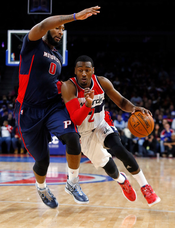 . Washington Wizards guard John Wall (2) drives on Detroit Pistons center Andre Drummond (0) in the second half of an NBA basketball game in Auburn Hills, Mich., Sunday, Feb. 22, 2015. (AP Photo/Paul Sancya)