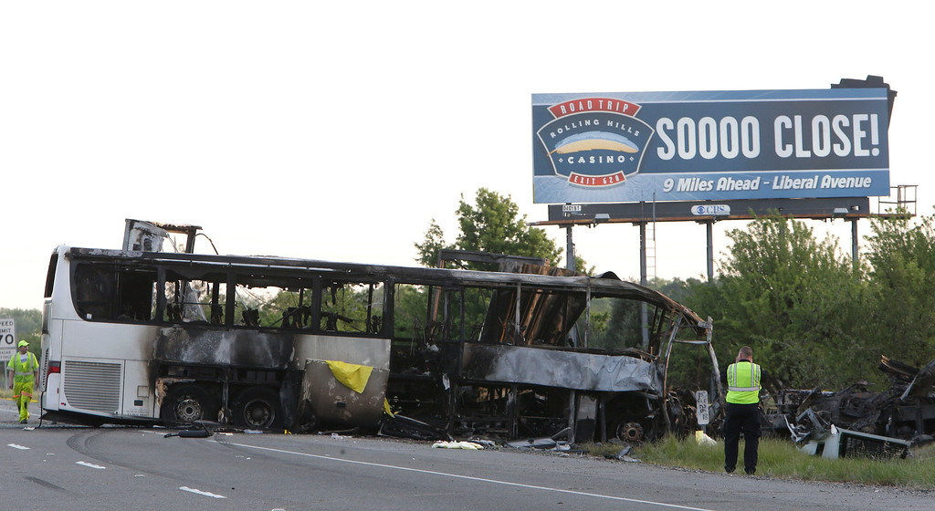 . A California Highway Patrol Officer photographs the crash scene, Friday, April 11, 2014, where a tour bus and a FedEX truck crashed on Interstate 5 Thursday in Orland, Calif.  At least ten people were killed and dozens injured in the fiery crash between the truck and a bus carrying high school students on a visit to a Northern California College.(AP Photo/Rich Pedroncelli)