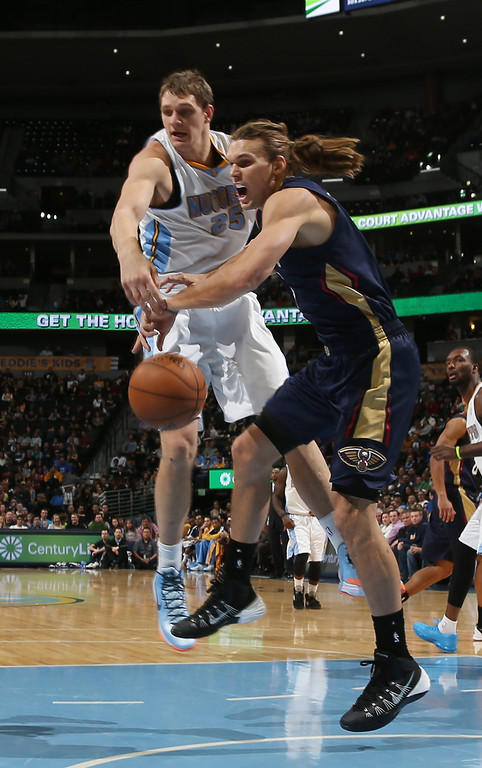 . New Orleans Pelicans forward Louis Amundson, front, battles for control of a loose ball with Denver Nuggets center Timofey Mozgov, of Russia, in the first quarter of an NBA basketball game in Denver on Sunday, Dec. 15, 2013. (AP Photo/David Zalubowski)