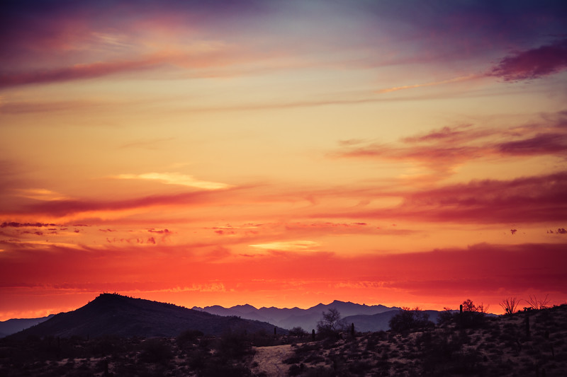 A sunset over a distant mountain