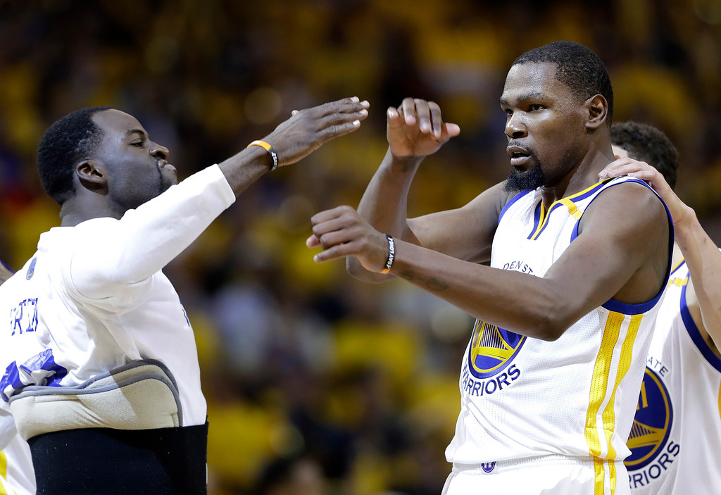. Golden State Warriors forward Kevin Durant, center, celebrates with Draymond Green, left, and Klay Thompson during the second half of Game 2 of basketball\'s NBA Finals against the Cleveland Cavaliers in Oakland, Calif., Sunday, June 4, 2017. (AP Photo/Marcio Jose Sanchez)