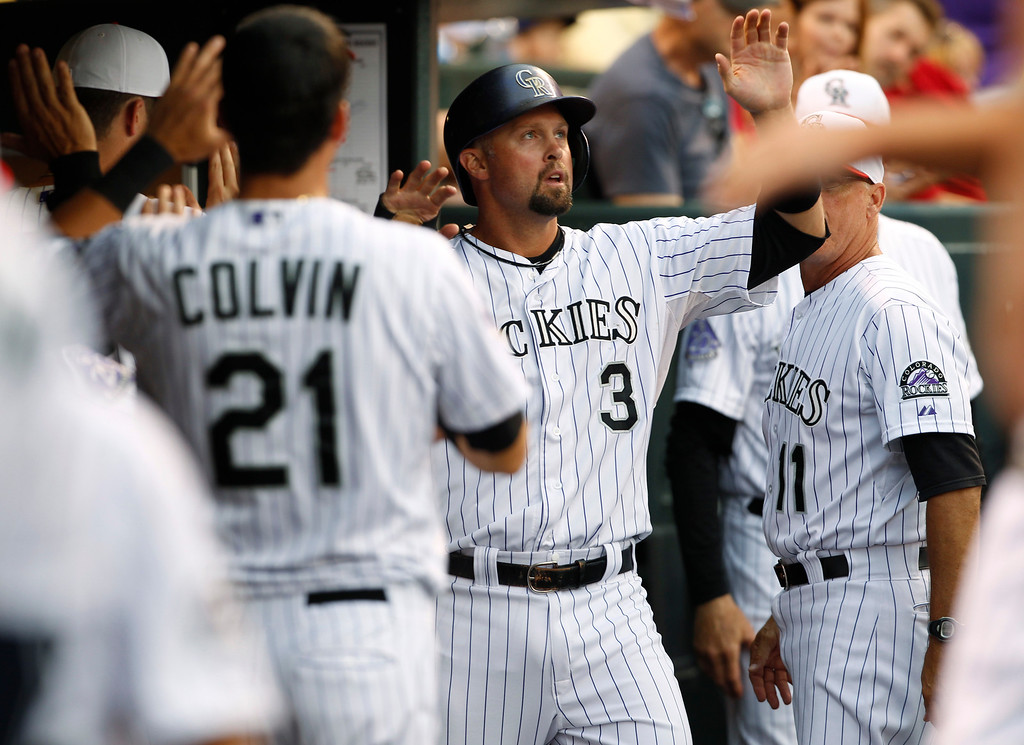 . Colorado Rockies\' Michael Cuddyer, center, is congratulated after scoring on a single by Wilin Rosario against the Los Angeles Dodgers in the third inning of a baseball game in Denver, Thursday, July 4, 2013. Cuddyer contributed to the third-inning rally with a double to drive in two runs. (AP Photo/David Zalubowski)
