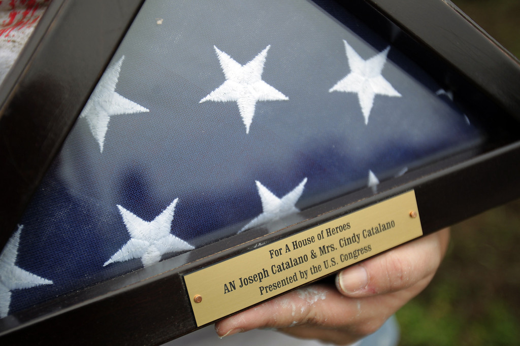 . Susan Gerkin, of Fort Benning, Ga., executive director of House of Heroes holds a U.S. flag that was flown over the nation\'s Capitol which will be presented home owners Navy veteran Joseph Catalano and wife Cindy Catalano in Hayward, Calif., on Thursday, Jan. 24, 2013. The Columbus, Ga. nonprofit House of Heroes is partnering with Home Depot to repair 36 houses owned by military and public safety veteran or their spouses  around the nation. (Anda Chu/Staff)
