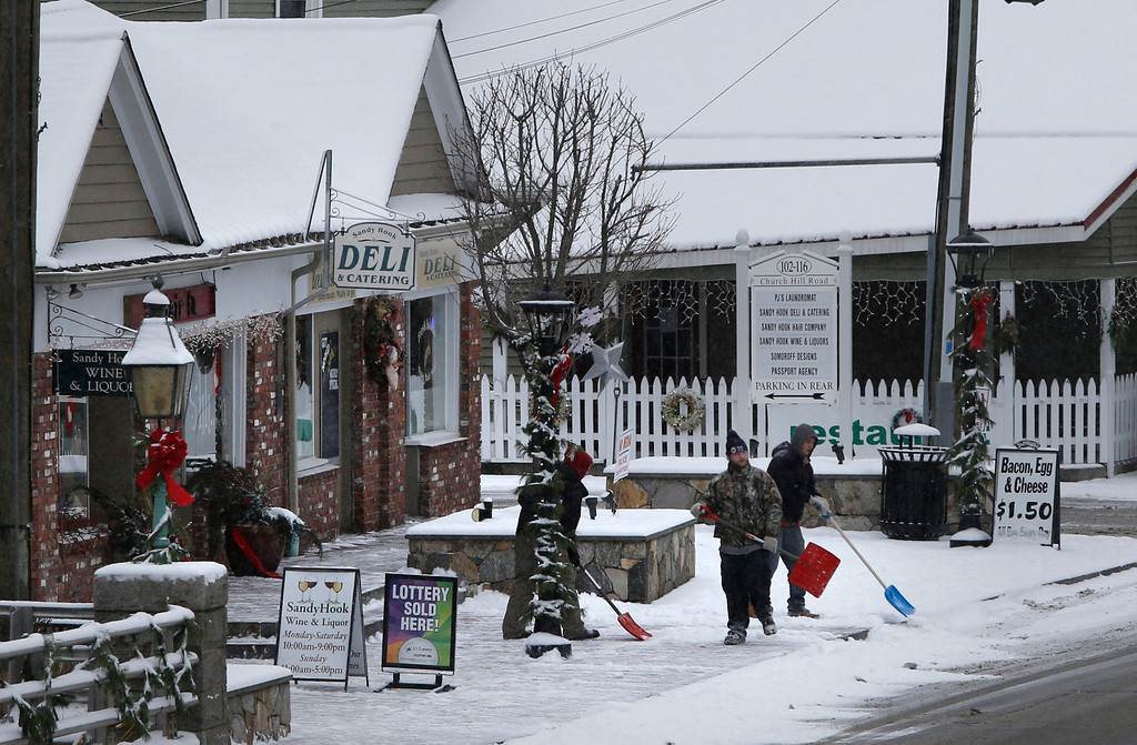 . Men shovel snow in Newtown, Conn., Saturday, Dec. 14, 2013.  Bells tolled 26 times to honor the children and educators killed one year ago in a shooting rampage at Sandy Hook Elementary School as local churches held memorial services. With snow falling and homes decorated with Christmas lights, Newtown looked every bit the classic New England town. But reminders of the private grief were everywhere.  (AP Photo/Robert F. Bukaty)
