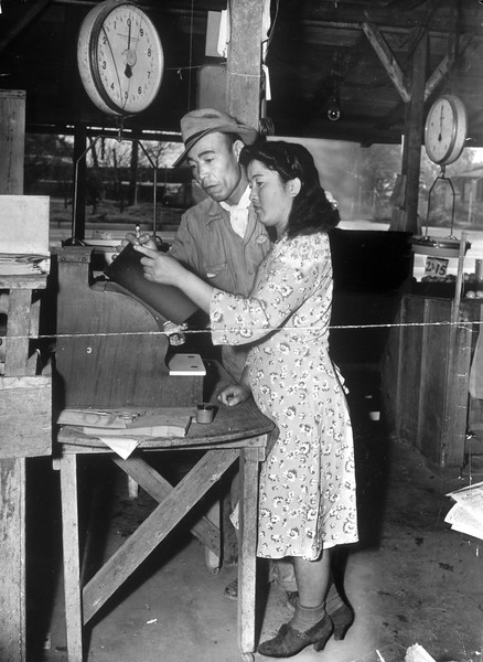 """""""George Hickey, Japanese alien who operates vegetable stand in prohibited area opposite Vultee plane factory, shown with his Nisei wife, Mrs. May Hickey, who will take over business when he leaves.""""--caption on photograph"""