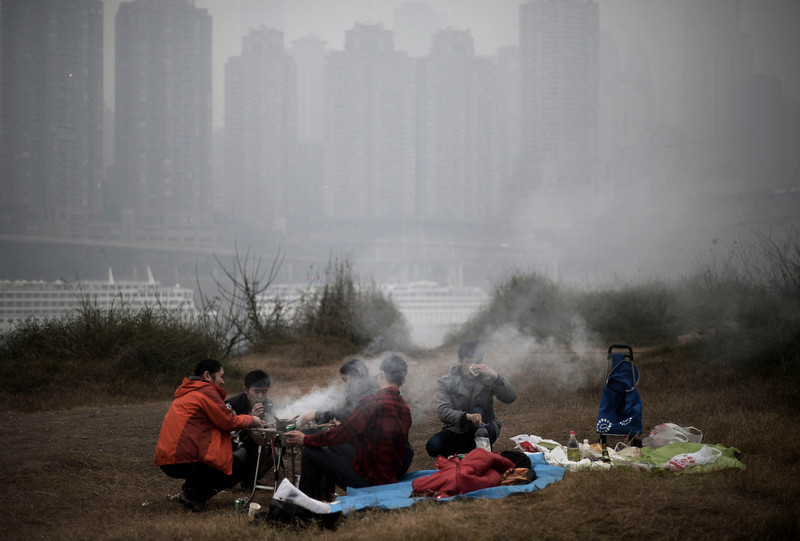 """. In this photo taken Sunday Feb. 23, 2014, residents barbecue along the river bank during a hazy day in southwest China\'s Chongqing municipality. Xinhua said that almost all provinces in central and east China have had serious air pollution since Friday, and that Beijing and five provinces in northern and eastern China had reported \""""severe smog.\"""" (AP Photo)"""