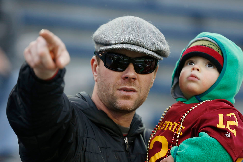 . Iowa State fan Mark Seacat tries to direct his son West\'s gaze to the field, but the young boy looks into the stands prior to the Liberty Bowl NCAA college football game featuring Iowa State and Tulsa, in Memphis, Tenn., Monday, Dec. 31, 2012. (AP Photo/Rogelio V. Solis)