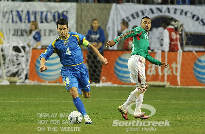 Mexico's Forward Edgar Pacheco (#13) watches as he lets Bosnia-Herzegovina's Defencer Emir Spahic (#4) go by him in Soccer action between Bosnia-Herzegovina and Mexico.  Mexico defeated Bosnia-Herzegovina 2-0 in the game at the Georgia Dome in Atlanta, GA.