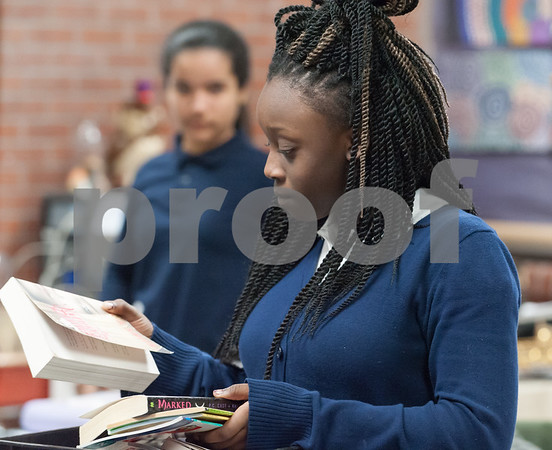 01/11/18 Wesley Bunnell | Staff 45 students from Slade Middle School participate in an American Savings Foundation funded program through the YWCA for youth development opportunities. Activities involve homework, social programs and team building activities. Jamie Luxier looks through a collection of books to read.