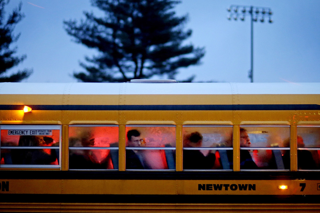 . People arrive on a school bus at Newtown High School for a memorial vigil attended by President Barack Obama for the victims of the Sandy Hook Elementary School shooting, Sunday, Dec. 16, 2012, in Newtown, Conn. A gunman walked into Sandy Hook Elementary School in Newtown Friday and opened fire, killing 26 people, including 20 children. (AP Photo/David Goldman)