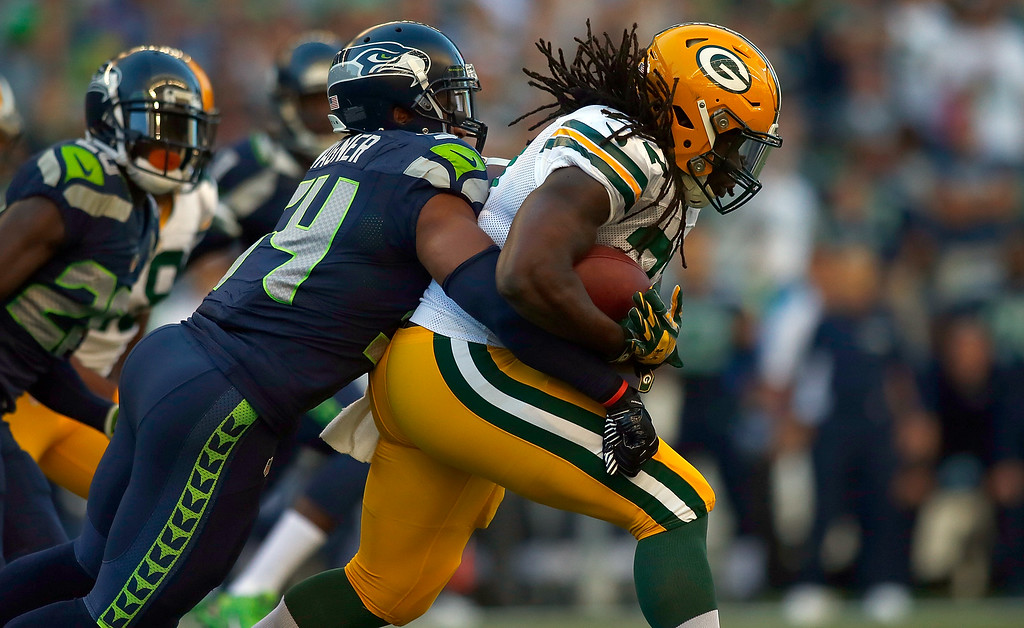 . SEATTLE, WA - SEPTEMBER 04:  Running back Eddie Lacy #27  of the Green Bay Packers is brought down by linebacker Bobby Wagner #54 of the Seattle Seahawks during the first quarter of the game at CenturyLink Field on September 4, 2014 in Seattle, Washington.  (Photo by Jonathan Ferrey/Getty Images)