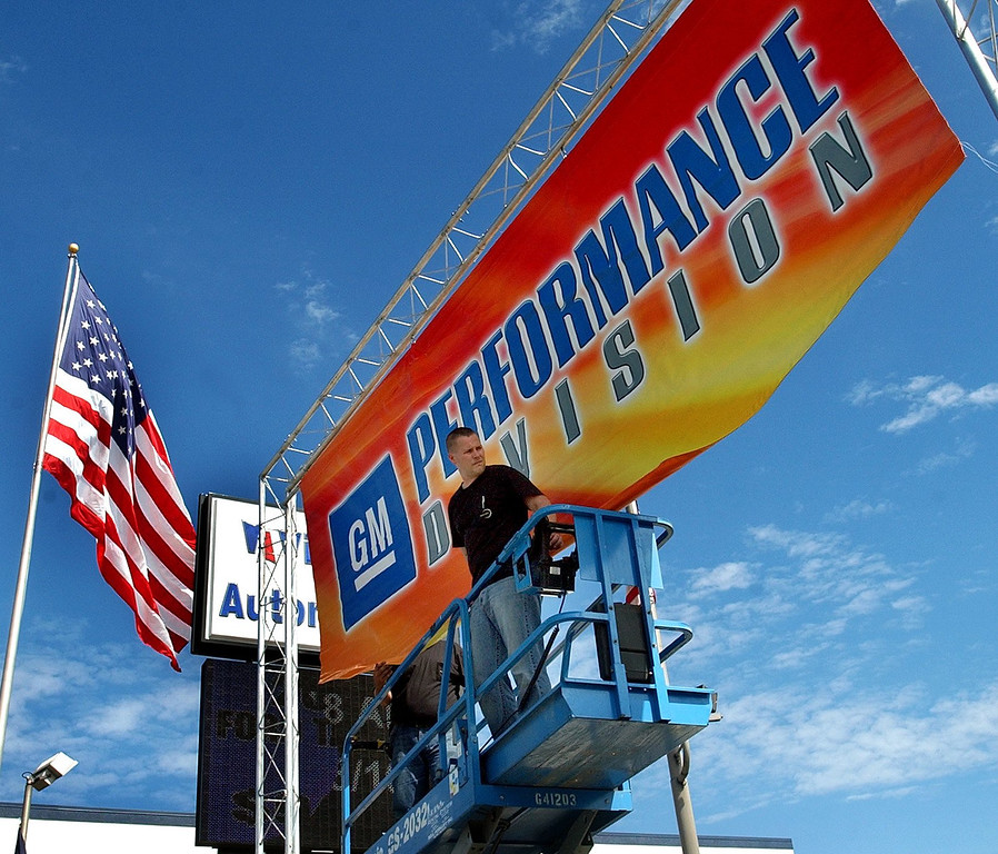 . Chad Wheeler hangs a banner at the GM Performance Division display near 13 Mile Road  and Woodward Avenue in Royal Oak for the upcoming Woodward Dream Cruise. (Oakland Press Photo: Vaughn Gurganian)