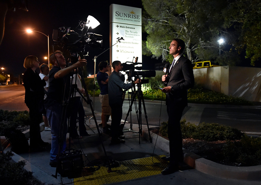 . Members of the media stand outside Sunrise Hospital and Medical Center while waiting for word about Lamar Odom on Tuesday, Oct. 13, 2015, in Las Vegas. Odom, a former NBA basketball player, was hospitalized after he was found unconscious at a Nevada brothel, authorities said. (AP Photo/David Becker)