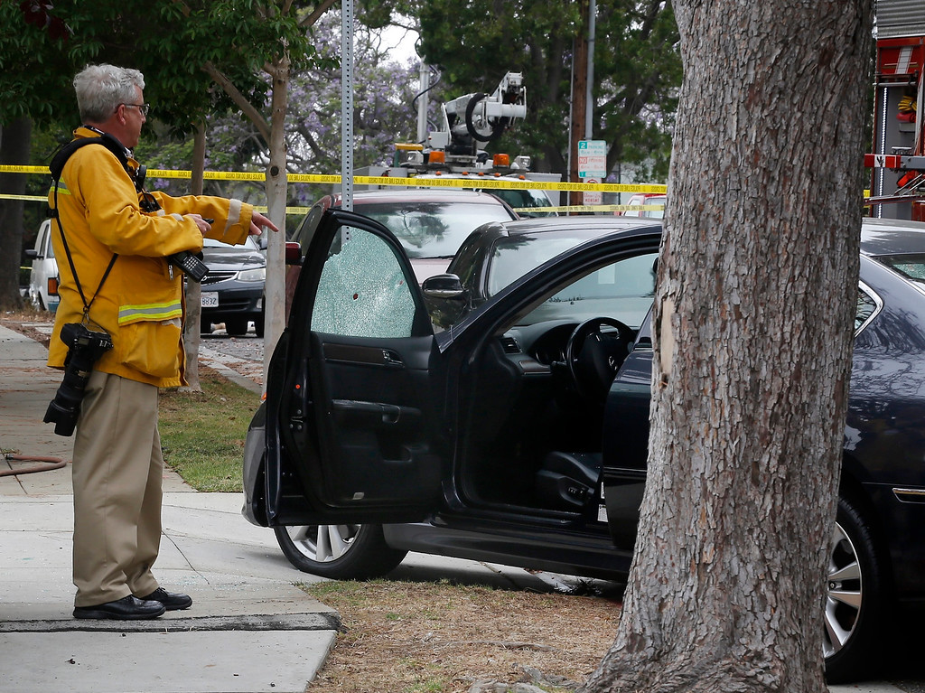 . An investigator checks a car damaged by a bullet at the intersection of Kansas and Yorkshire about a mile northeast of Santa Monica College in Santa Monica, Calif. on Friday, June 7, 2013. (AP Photo/Reed Saxon)
