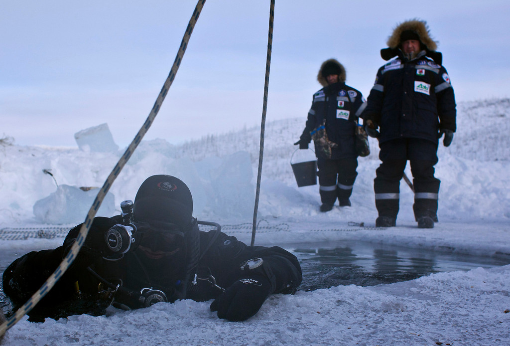 . Alexander Gubin, 43, prepares to dive into the frozen Labynkyr lake, some 100 km south from Oymyakon in the Republic of Sakha, northeast Russia, February 1, 2013. The coldest temperatures in the northern hemisphere have been recorded in Sakha, the location of the Oymyakon valley, where according to the United Kingdom Met Office a temperature of -67.8 degrees Celsius (-90 degrees Fahrenheit) was registered in 1933 - the coldest on record in the northern hemisphere since the beginning of the 20th century. Yet despite the harsh climate, people live in the valley, and the area is equipped with schools, a post office, a bank, and even an airport runway (albeit open only in the summer).    Picture taken February 1, 2013.    REUTERS/Maxim Shemetov