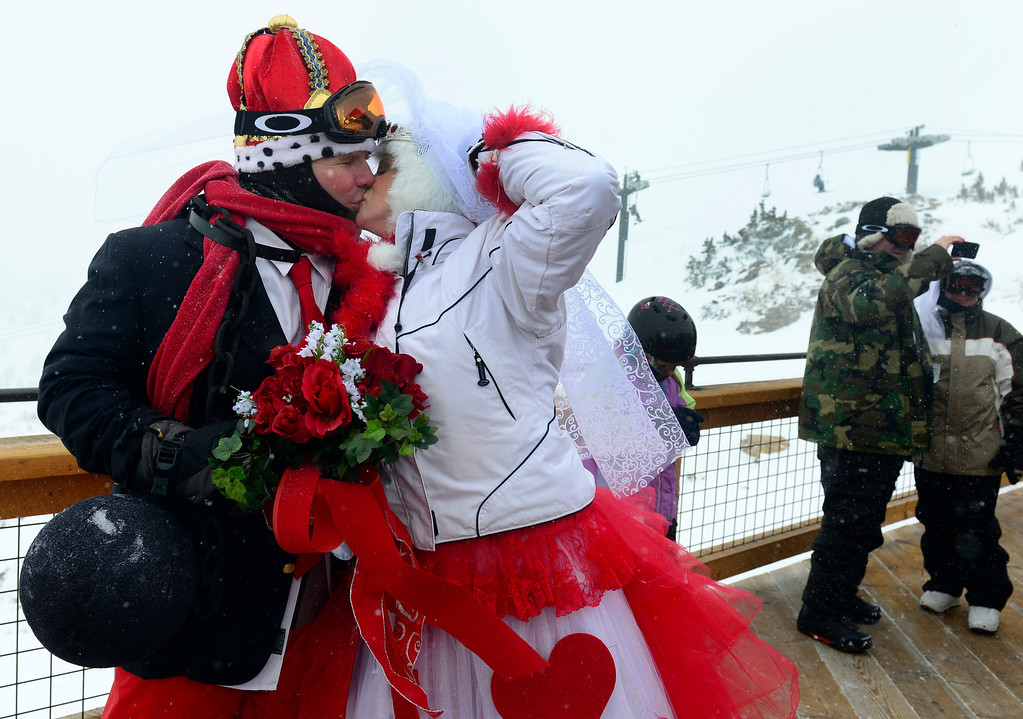 ". GEORGETOWN, CO - FEBRUARY 14: Dave Sitarski and his bride Kris Slager from Evergreen share a kiss before the start of the ceremony. Dozens of couples decided to say ""I do\"" for the first time or repeat their wedding vows on Valentines Day at the 23rd Annual Mountaintop Matrimony at Loveland Basin ski area. The couples hovered together to keep warm with white-out conditions at 12, 050 feet just outside the Ptarmagin Roost cabin at the top of chairlift #2 with the minister Harry Heilman officiating. (Photo by Kathryn Scott Osler/The Denver Post)"