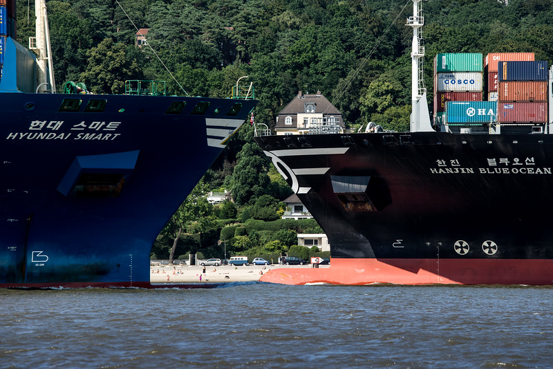 2 Containerschiffe begegnen sich auf der Elbe vor einem Sandstrand von Blankenese
