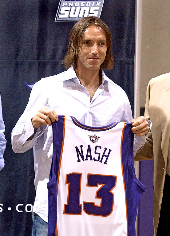. Newly aquired Phoenix Suns guard Steve Nash, right, holds up his new jersey Wednesday, July 14, 2004 at America West Arena in Phoenix.  (AP Photo/Matt York)