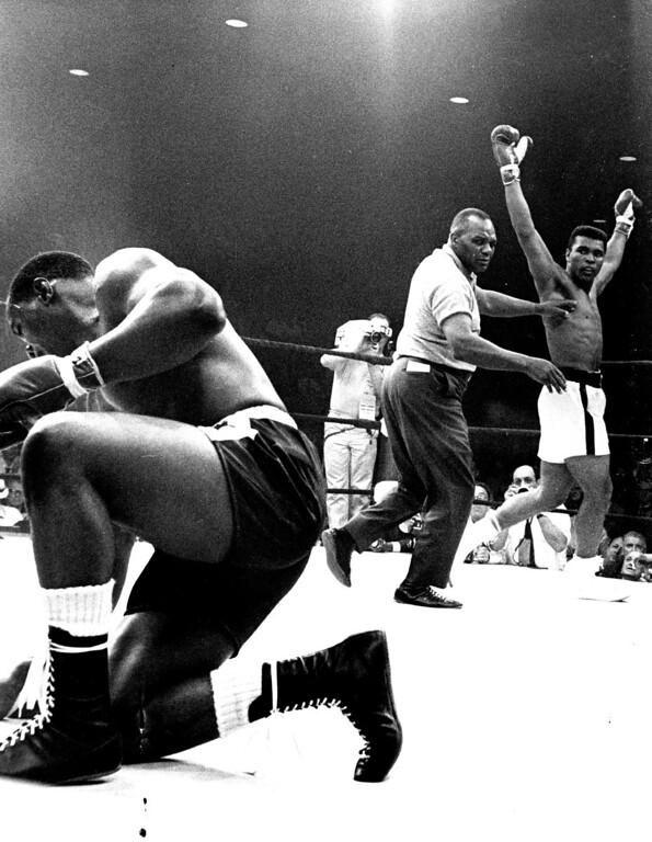 . LEWISTON, MAINE:  Referee Joe Walcott guides heavyweight champion Cassius Clay to a neutral corner after Clay downed challenger Sonny Liston (struggling to his feet) in the first round of their championship bout here May 25th., 1965. Clay retained his crown by scoring a one-minute knockout victory over Liston in the controversial fight. Denver Post Library photo archive