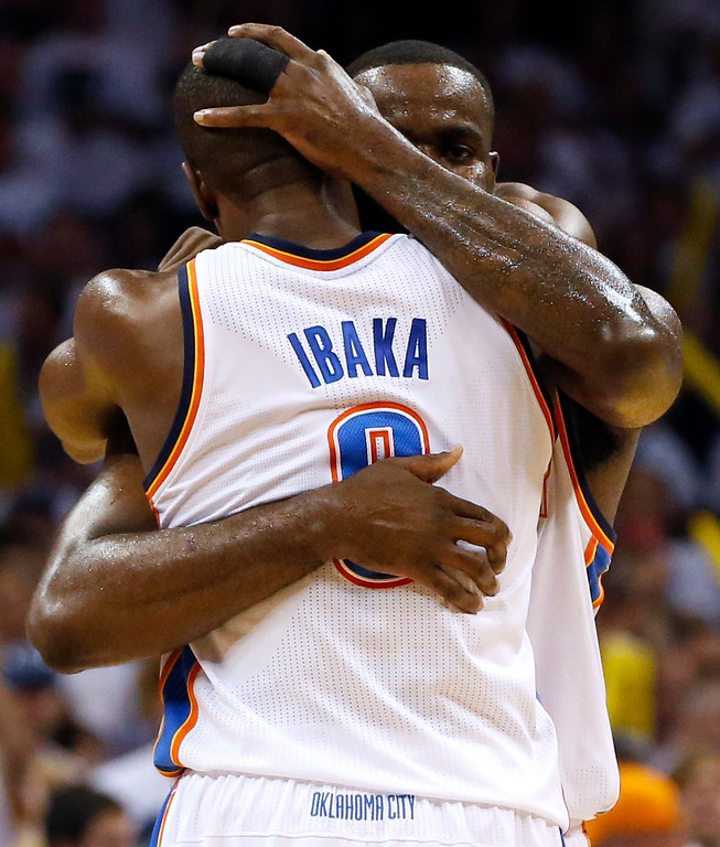. Oklahoma City Thunder forward Serge Ibaka (9) and Kendrick Perkins, rear, embrace in the first half against the San Antonio Spurs during Game 6 of the Western Conference finals NBA basketball playoff series, in Oklahoma City, Saturday, May 31, 2014. (AP Photo/Sue Ogrocki)