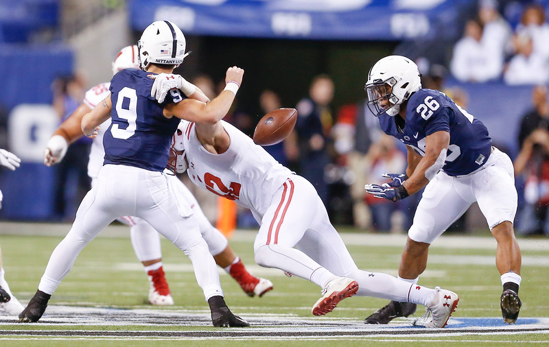 Penn State Nittany Lions quarterback Trace McSorley (9) is hit hard by Wisconsin Badgers linebacker T.J. Watt (42) and fumbled the ball during the first half of the Wisconsin Badgers against the Penn State Nittnay Lions for the Big Ten football championship at Lucas Oil Stadium in Indianapolis, Ind., Saturday, Dec. 3, 2016. (Photo by Sam Riche)