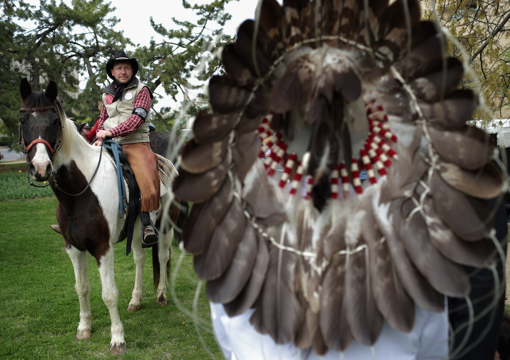". Members of the Cowboy and Indian Alliance, including Native Americans, farmers and ranchers from across the United States, prepare for a horseback ride to demonstrate against the proposed Keystone XL pipeline in front of the U.S. Capitol April 22, 2014 in Washington, DC. As part of its ""Reject and Protect\"" protest, the Cowboy and Indian Alliance is organizing a weeklong series of actions by farmers, ranchers and tribes to show their opposition to the pipeline.  (Photo by Chip Somodevilla/Getty Images)"