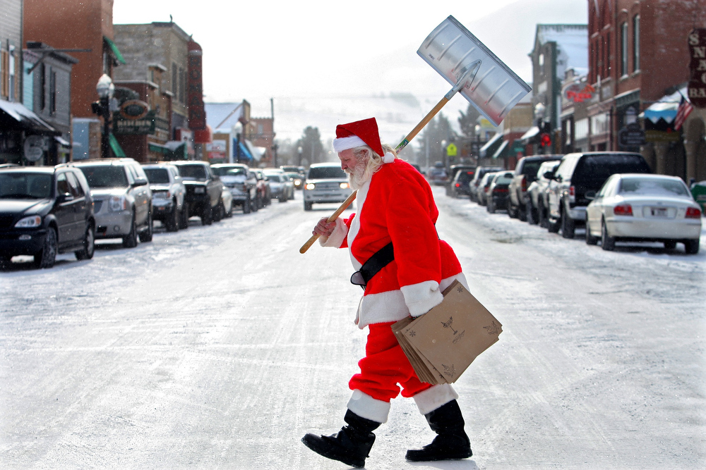Description of . Gordie Blevins, dressed as Santa Claus for a breakfast with Santa event in Red Lodge, Mont. Saturday, December 1, 2007, carries a shovel across Broadway after shoveling the sidewalks in front of  his businesses. The Red Lodge and Billings area received at least one inch of snow Saturday. (AP Photo/The Gazette, Casey Riffe )