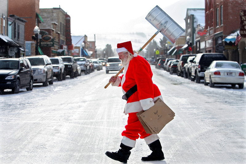 . Gordie Blevins, dressed as Santa Claus for a breakfast with Santa event in Red Lodge, Mont. Saturday, December 1, 2007, carries a shovel across Broadway after shoveling the sidewalks in front of  his businesses. The Red Lodge and Billings area received at least one inch of snow Saturday. (AP Photo/The Gazette, Casey Riffe )