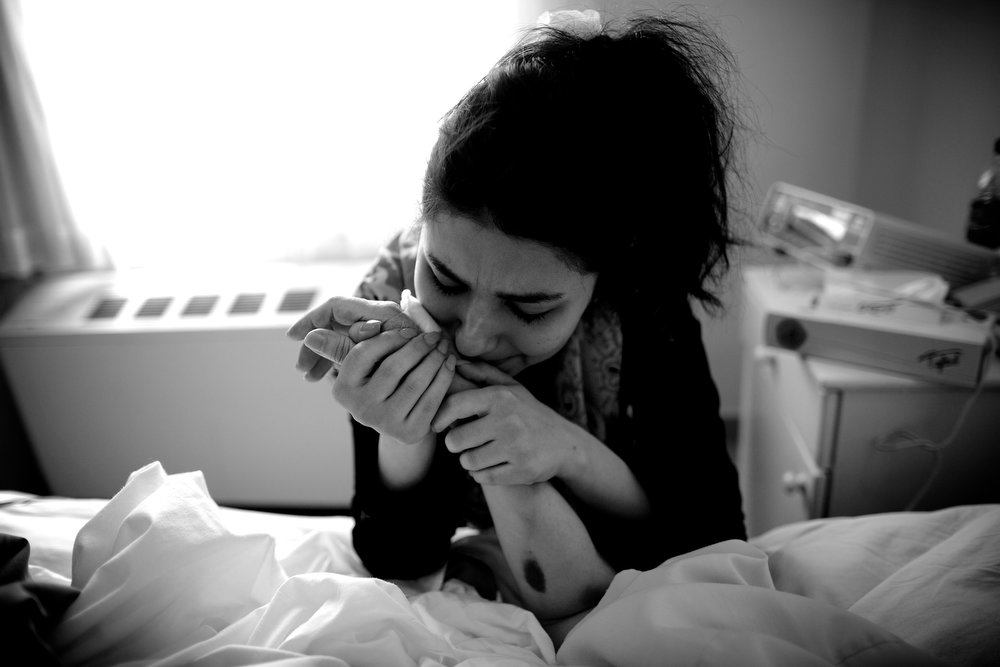 . Sara cries as she kisses the hand of her mother Soheila Mehri, who suffers from breast cancer, in a hospital in Tehran on April 11, 2013.  AFP PHOTO/BEHROUZ MEHRI