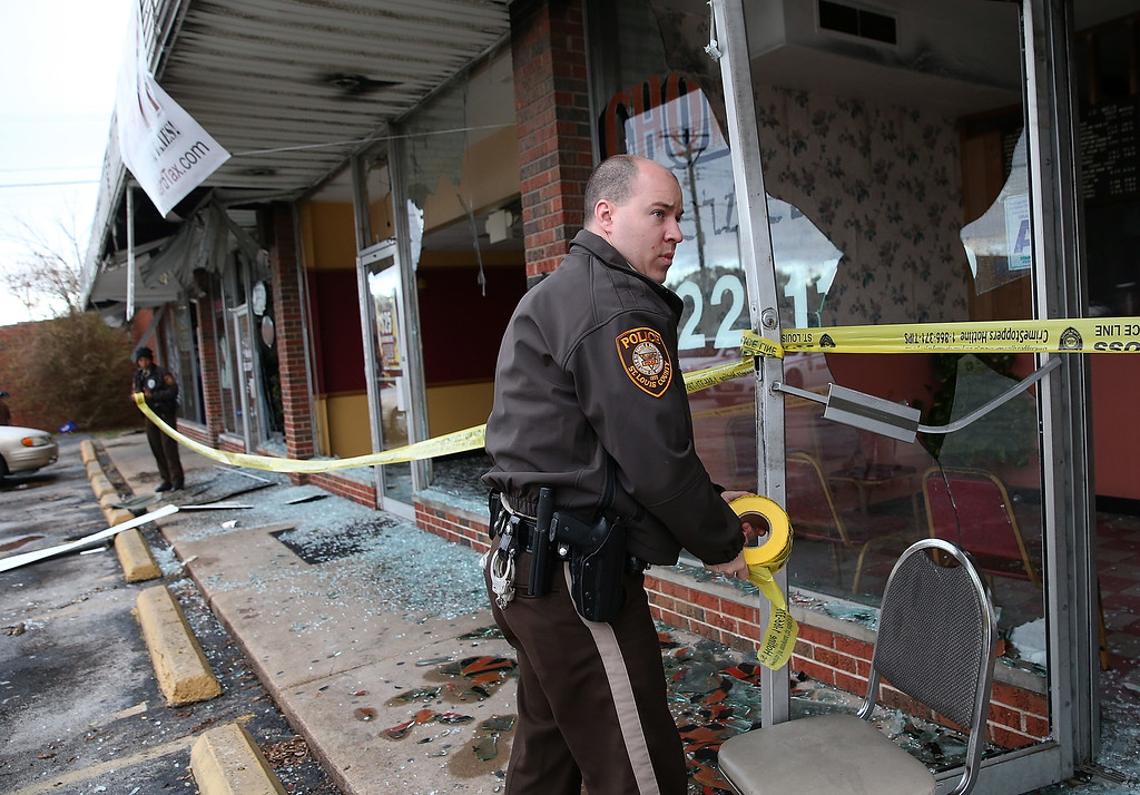 . A St. Louis county police officer uses police tape to secure a building that was burned during a demonstration on November 25, 2014 in Dellwood, Missouri. Demonstrators caused extensive damage last night in Ferguson and surrounding areas after a St. Louis County grand jury decided to not indict Ferguson police Officer Darren Wilson in the shooting of Michael Brown. (Photo by Justin Sullivan/Getty Images)