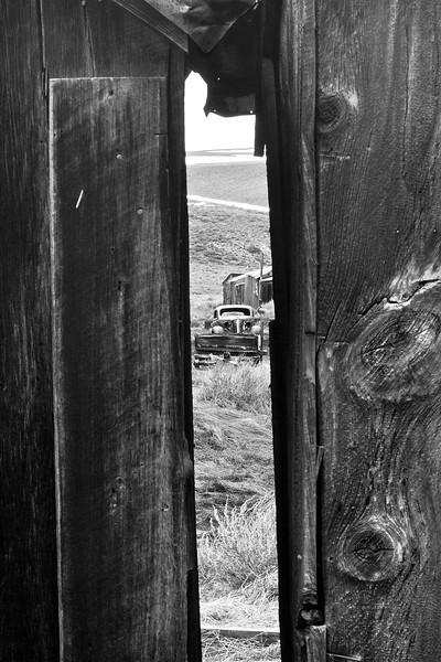 Rusting car thru an outhouse slot