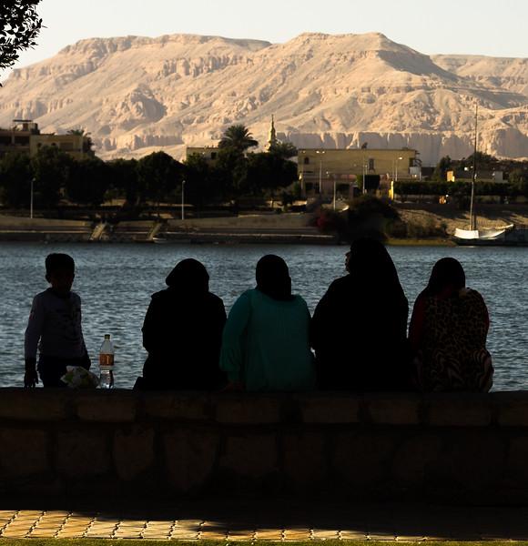 Mujeres con niño a la sombra junto al Nilo