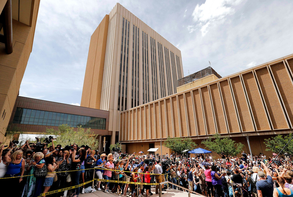 . Spectators wait outside Superior Court in Phoenix, Wednesday, May 8, 2013 for a verdict in the trial of Jodi Arias, a waitress and aspiring photographer charged with killing her boyfriend, Travis Alexander, in Arizona in 2008. The four month trial included graphic details of their sexual escapades and photos of Alexander just after his death. (AP Photo/Matt York)