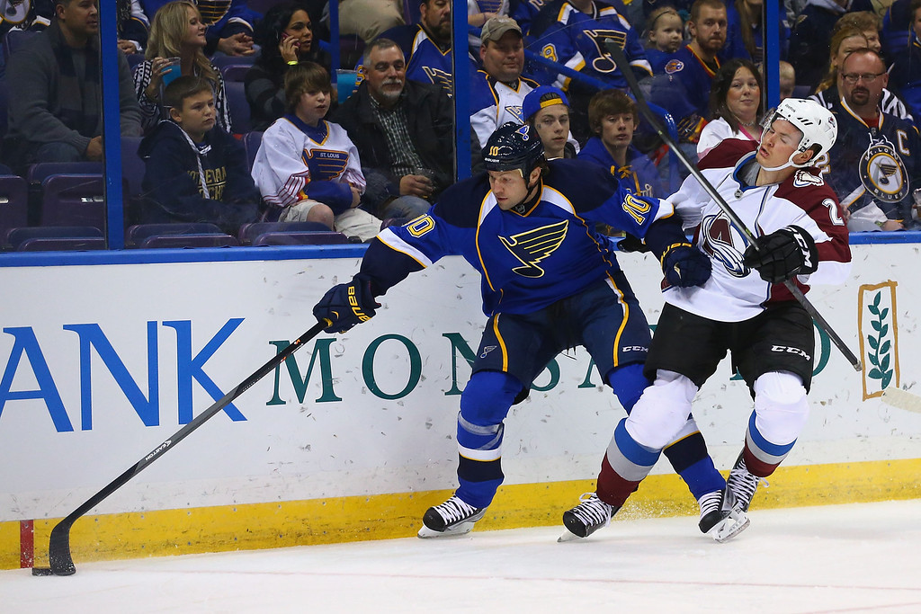 . ST. LOUIS, MO - NOVEMBER 14:  Brenden Morrow #10 of the St. Louis Blues pushes Nick Holden #2 of the Colorado Avalanche to the ice while chasing a loose puck at the Scottrade Center on November 14, 2013 in St. Louis, Missouri.  (Photo by Dilip Vishwanat/Getty Images)