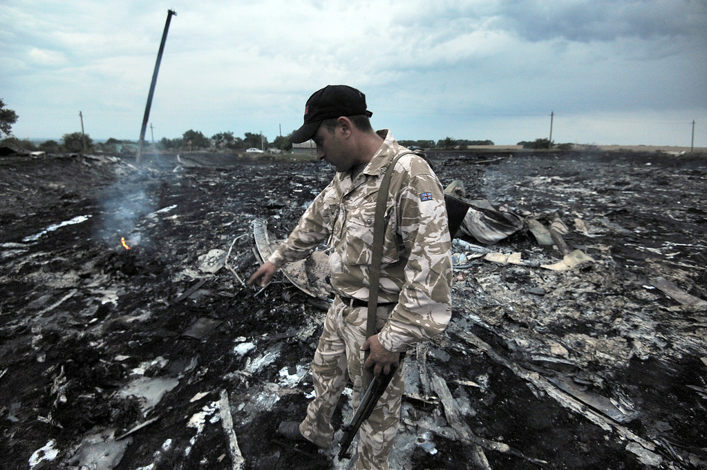 . A man wearing military fatigues points to the wreckage of the malaysian airliner carrying 295 people from Amsterdam to Kuala Lumpur after it crashed, near the town of Shaktarsk, in rebel-held east Ukraine. Pro-Russian rebels fighting central Kiev authorities claimed on Thursday that the Malaysian airline that crashed in Ukraine had been shot down by a Ukrainian jet. AFP PHOTO/DOMINIQUE FAGET  /AFP/Getty Images