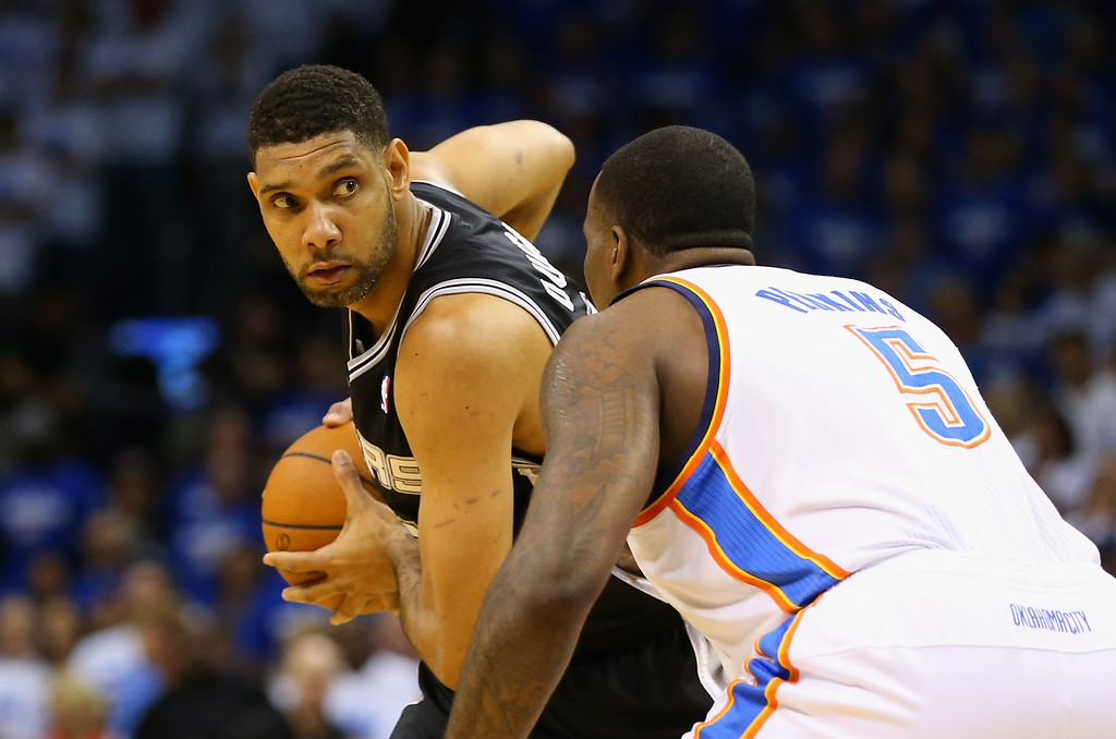 . OKLAHOMA CITY, OK - MAY 27: Tim Duncan #21 of the San Antonio Spurs handles the ball against Kendrick Perkins #5 of the Oklahoma City Thunder in the first quarter during Game Four of the Western Conference Finals of the 2014 NBA Playoffs at Chesapeake Energy Arena on May 27, 2014 in Oklahoma City, Oklahoma. NOTE TO USER: User expressly acknowledges and agrees that, by downloading and or using this photograph, User is consenting to the terms and conditions of the Getty Images License Agreement. (Photo by Ronald Martinez/Getty Images)