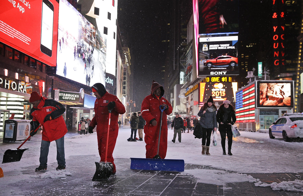 . Men shovel a pedestrian walkway in New York\'s Times Square on Monday, Jan. 26, 2015. More than 35 million people along the Philadelphia-to-Boston corridor rushed to get home and settle in Monday as a fearsome storm swirled in with the potential for hurricane-force winds and 1 to 3 feet of snow that could paralyze the Northeast for days. (AP Photo/Seth Wenig)