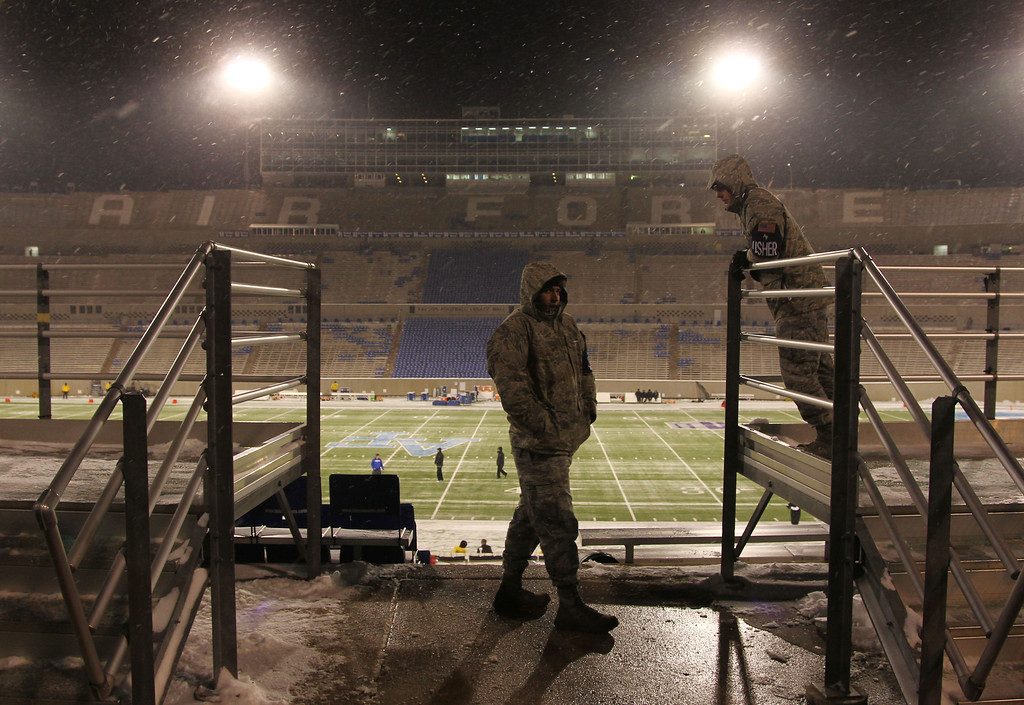 . Airmen wait for fans to show up as snow and cold envelop Falcon Stadium before Air Force hosts UNLV in the first quarter of an NCAA football game at Air Force Academy, Colo., on Thursday, Nov. 21, 2013. (AP Photo/David Zalubowski)