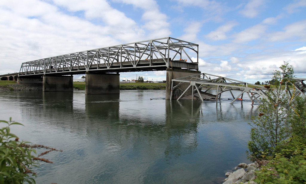 . A span of highway bridge sits in the Skagit River May 24, 2013 after collapsing near the town of Mt Vernon, Washington late Thursday. The bridge collapse that sent cars and drivers tumbling into a frigid river in Washington state appears to have been caused when a semi-trailer truck carrying an oversize load struck a bridge support beam, officials said on Friday. The truck crossed the bridge safely before a portion of the structure collapsed, sending two vehicles and a mass of concrete and steel into the Skagit River Thursday evening. Three people had to be rescued, officials said.   REUTERS/Cliff DesPeaux