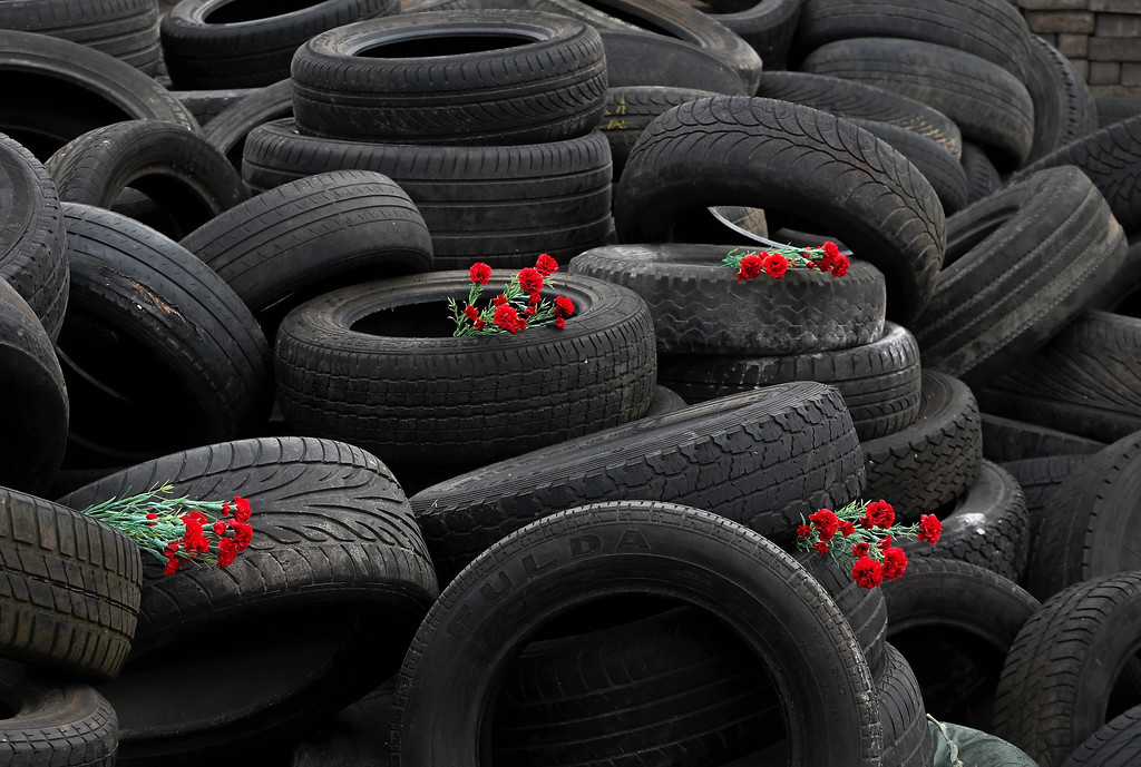 . Ukrainians laid flowers in between tires as they remember those killed during the recent violent protests, in Kiev, Ukraine, 26 February 2014. Former Ukrainian president Viktor Yanukovych had his first public appearance  in Rostov, Russia, since being ousted. He told the there he would fight for his country and insisted he was not overthrown.  EPA/SERGEY DOLZHENKO
