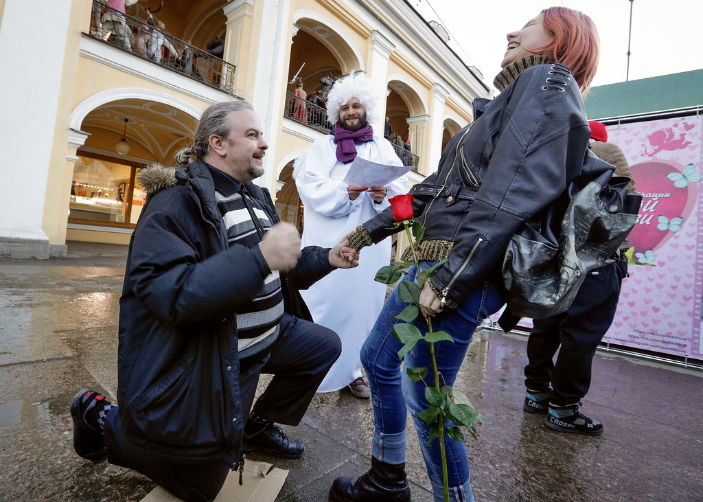 . A couple confesses their love to each other to get a \'Certificate of eternal love\' during a flash mob to mark Valentine\'s Day in St. Petersburg, Russia, Tuesday, Feb. 14, 2017. (AP Photo/Dmitri Lovetsky)