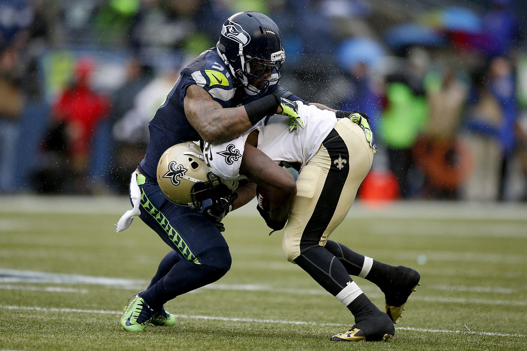 . SEATTLE, WA - JANUARY 11:  Running back Khiry Robinson #29 of the New Orleans Saints runs the ball against outside linebacker Bruce Irvin #51 of the Seattle Seahawks in the first half during the NFC Divisional Playoff Game at CenturyLink Field on January 11, 2014 in Seattle, Washington.  (Photo by Otto Greule Jr/Getty Images)