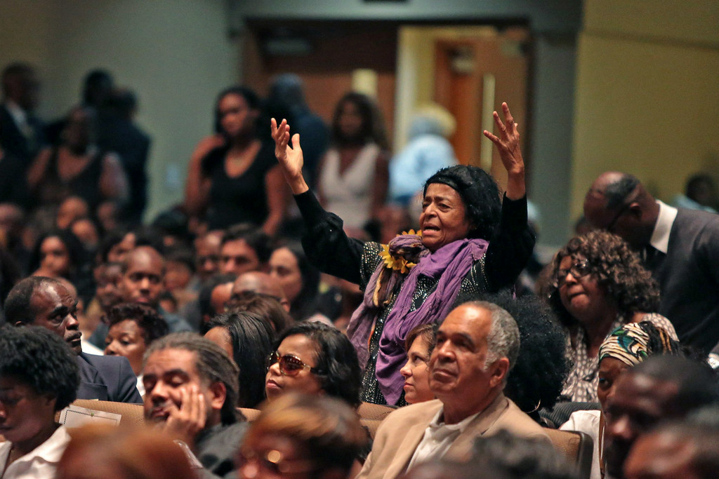 . A woman rises to her feet during the funeral of Michael Brown inside Friendly Temple Missionary Baptist Church on August 25, 2014 in St. Louis Missouri. Michael Brown, an 18 year-old unarmed teenager, was shot and killed by Ferguson Police Officer Darren Wilson in the nearby town of Ferguson, Missouri on August 9. His death caused several days of violent protests along with rioting and looting in Ferguson.  (Photo by Robert Cohen-Pool/Getty Images)