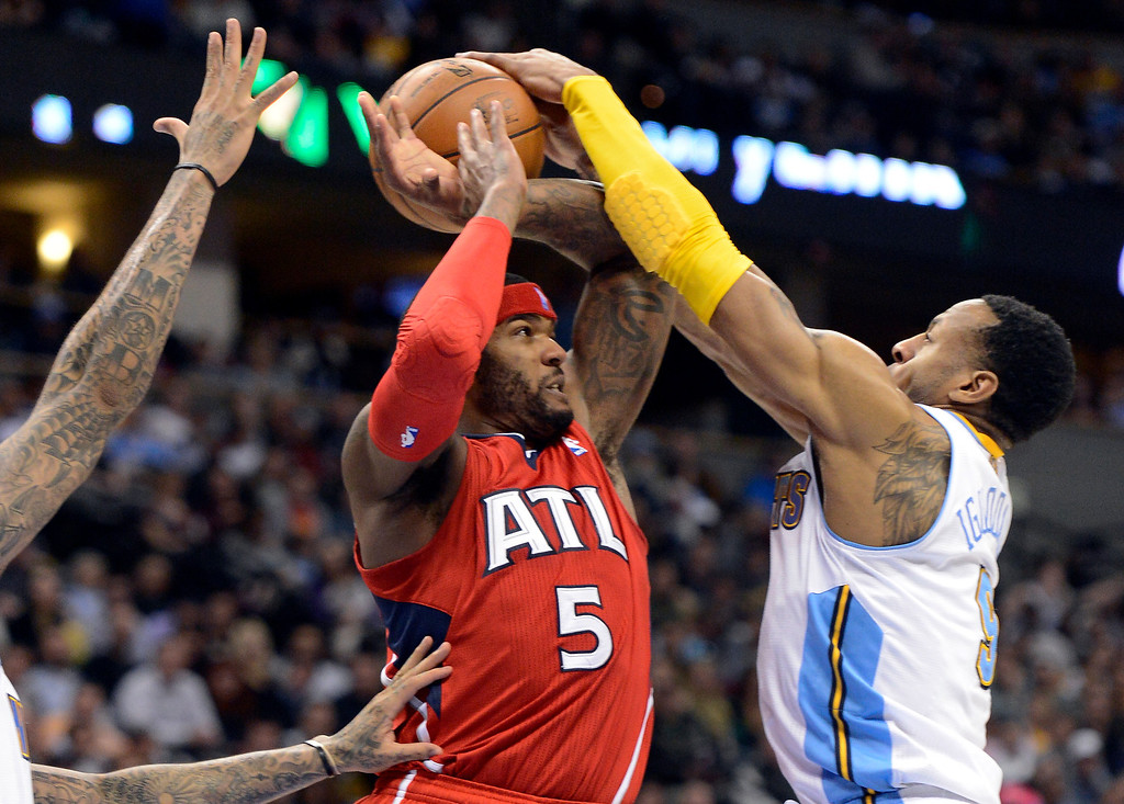. Josh Smith (5) of the Atlanta Hawks gets his pass blocked by Andre Iguodala (9) of the Denver Nuggets during the third quarter March 4,  2013 at Pepsi Center. The Denver Nuggets defeated the Atlanta Hawks 104-88. (Photo By John Leyba/The Denver Post)