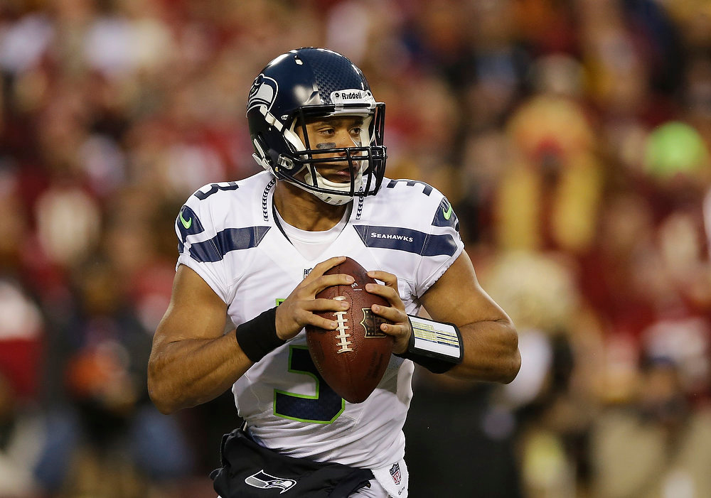 Description of . Seattle Seahawks quarterback Russell Wilson scrambles with the ball during the first half of an NFL wild card playoff football game against the Washington Redskins in Landover, Md., Sunday, Jan. 6, 2013. (AP Photo/Matt Slocum)