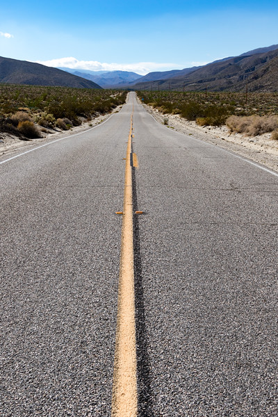 A road disappears into the distance with a solid and striped yellow line down the middle.
