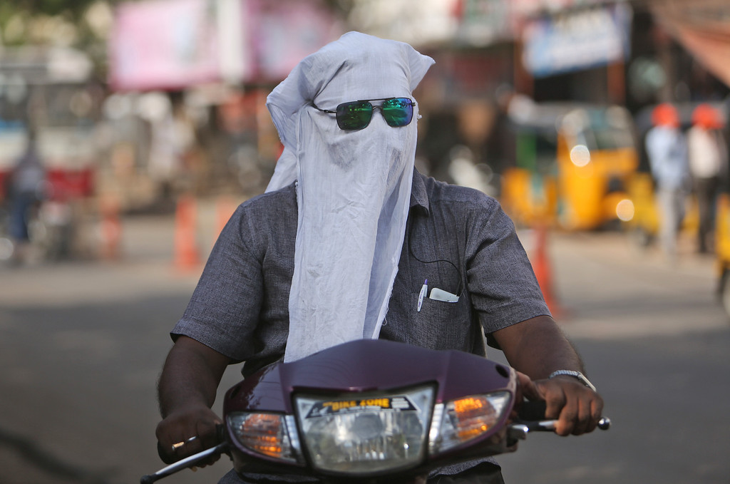 . A man rides a scooter with his face covered with a cloth to protect him from a heat wave in Hyderabad, India, Saturday, May 21, 2016. Authorities in a parched western Indian state sprinkled water in the streets and awaited the arrival of a special water train on Saturday, two days after temperatures reached a record-high 51 degrees Celsius (124 Fahrenheit). (AP Photo/ Mahesh Kumar A.)