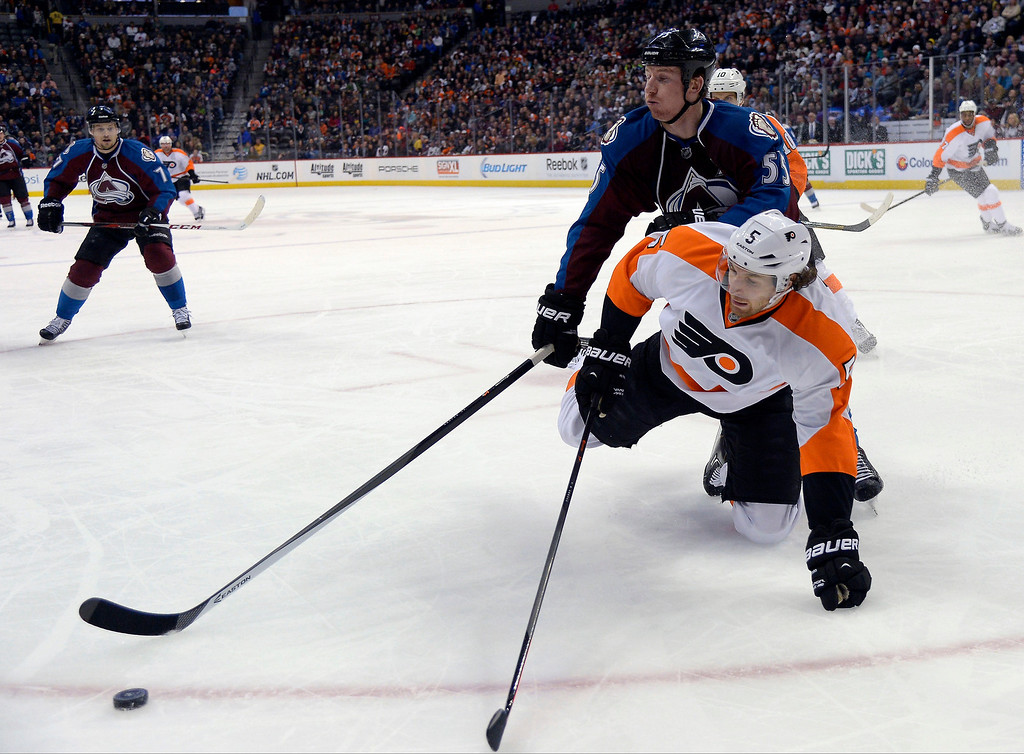 . Colorado Avalanche left wing Cody McLeod (55) knocks Philadelphia Flyers defenseman Braydon Coburn (5) to the ice during the first period January 2, 2014 at Pepsi Center. (Photo by John Leyba/The Denver Post)