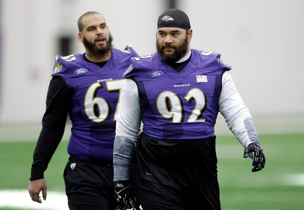 . Baltimore Ravens defensive end Haloti Ngata (92) walks off the field in front of teammate Lawrence Guy after an NFL football practice, Wednesday, Jan. 7, 2015, in Owings Mills, Md. The Ravens will travel to New England for a divisional playoff game against the Patriots on Saturday, Jan. 10. (AP Photo/Patrick Semansky)